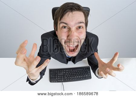 Angry And Frustrated Man Is Working With Computer And Shouting.