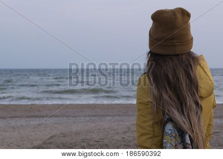 A European girl with long blond hair in a brown hat and mustard jacket with a backpack on her shoulders standing on the beach and looking at the sea