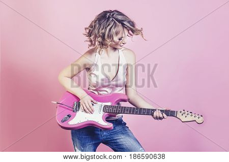 Beautiful woman blonde model with electric guitar and make up fashion on a pink background in Studio
