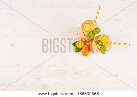 Orange citrus kumquat fruit smoothie in glass jars with straw mint leaf cute ripe berry top view. White wooden board background copy space.