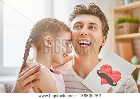 Happy father's day! Child daughter congratulates dad and gives him postcard. Daddy and girl smiling and hugging. Family holiday and togetherness.