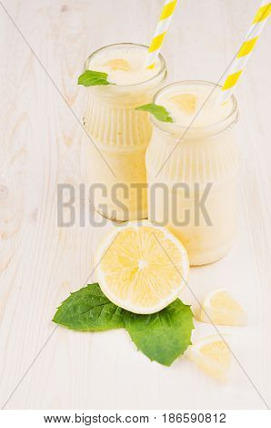 Freshly blended yellow lemon smoothie in glass jars with straw mint leaf cut lemon close up. White wooden board background vertical.