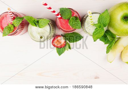 Decorative frame green and red fruit smoothie in glass jars with straw mint leaves of strawberry and apples top view. White wooden board background copy space.