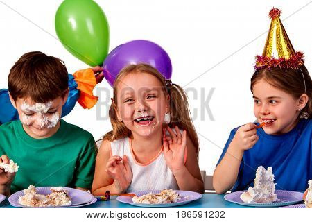 Birthday children celebrate party and eating cake on plate together . Portrait of three kids happy girl and boy in party hat sitting for table. Children got stained with festive cake.
