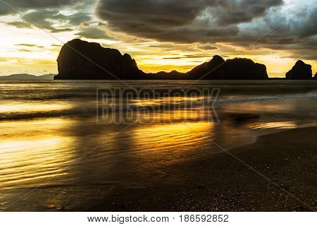 sunset at the sea beach with silhouette mountain