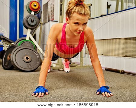 Stretching woman in sport gym. Girl doing push-up from floor. Woman workout at fitness class. Twist for women. Middle section of bare back. Body that you want concept. Girl uses sports supplements.