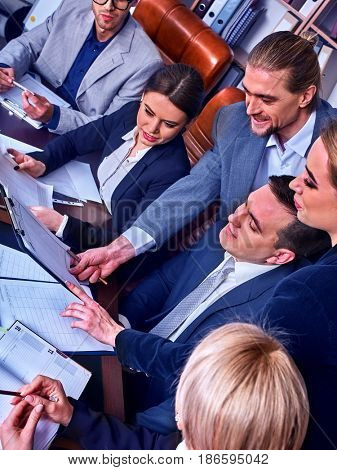 Business people office life of team people working with papers sitting table . Cabinets with folders background. Joyful business team in office discussing, sitting at table, upcoming business deal.