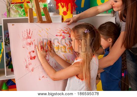 Children painting finger on easel. Group of kids girl and boy with teacher learn paint in class school. Child picture on background.