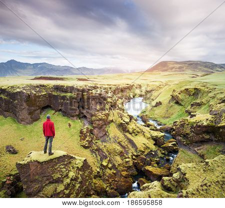 Skoga river over the Skogafoss waterfall, Iceland, Europe. Traveler in a red jacket stands on a rock and looks at the mountains