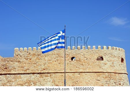 Part of Koules castle with a Greek flag in the foreground Heraklion Crete Greece Europe.