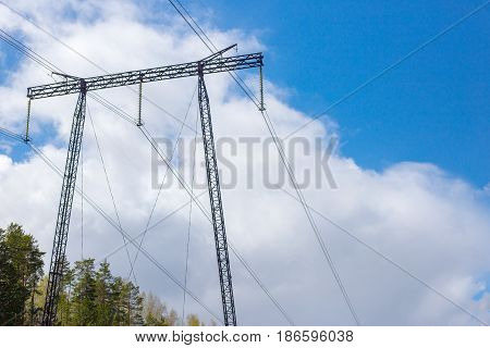 Support high-voltage power line on blue sky background, white clouds