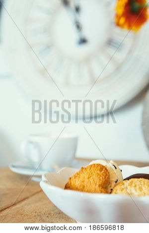 Table with cookie and white ceramic mug under clock. Vertical indoors shot.