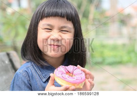 happiness face of asian children with sweet donut in hand