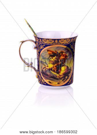 mug with a painting and a spoon for tea on white background