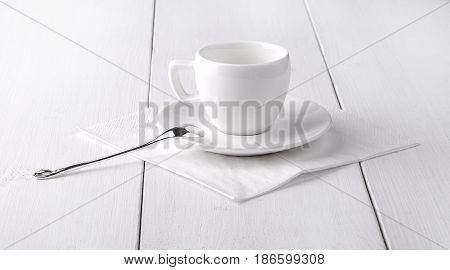 White empty cup of coffee on a white napkin