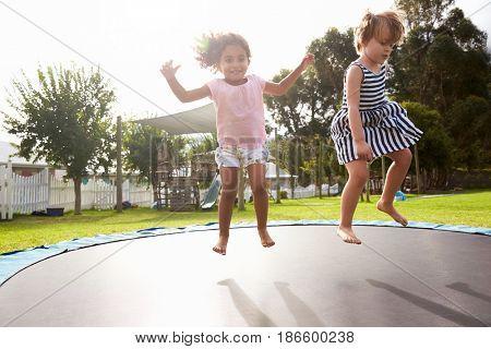 Children At Montessori School Having Fun On Outdoor Trampoline