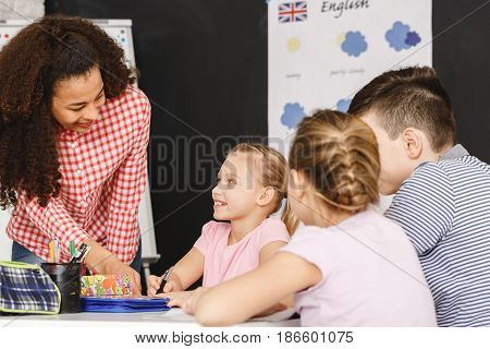 Teacher Helping Kids During Lesson