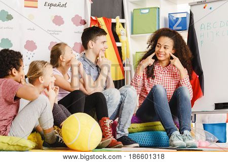 Teacher Gesturing Smile To The Kids