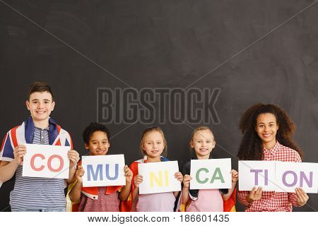 Cheerful children and teacher holding communication inscription together