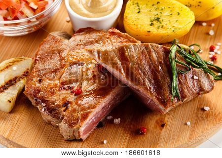 Grilled beefsteak with potatoes on wooden board