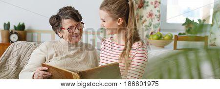 Grandma And Granddaughter Watching Photo Album