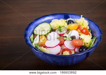 Fresh salad with vegetables on brown desk
