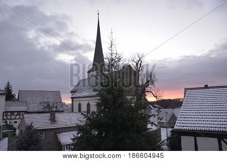 Sunrise over snow covered rooftops in January in Bavaria, Germany