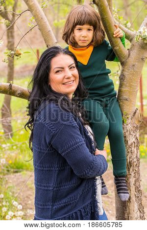 Mother with her son climbing in tree having fun in the garden