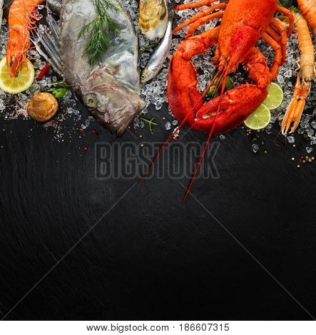 Whole lobster with seafood, mussels, prawns, fish, steak, sardine and other shells served on black stone