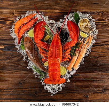 Fresh seafood, lobster, mussels, fish, prawns, and other shells in heart shape. Served on old wooden planks. Concept of seafood and love symbol