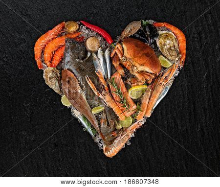 Fresh seafood, mussels, prawns, fish, crab, salmon steak, mackerel and other shells in heart shape. Served on black stone. Concept of seafood and love symbol
