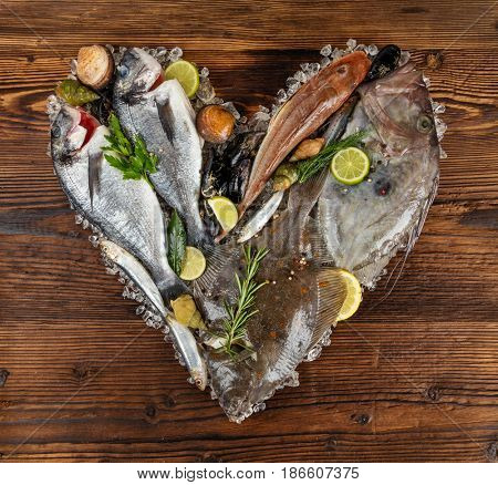 Fresh seafood, mussels, fish, mackerel, bream fish and other shells in heart shape. Served on old wooden planks. Concept of seafood and love symbol