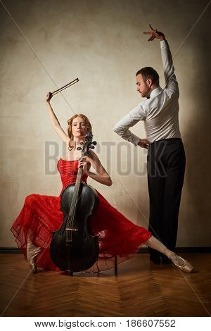 Female ballet dancer in red dress and pointe playing on antique black cello and male dancing latin