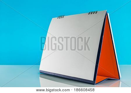 Blank paper desk calendar on table with blue background.