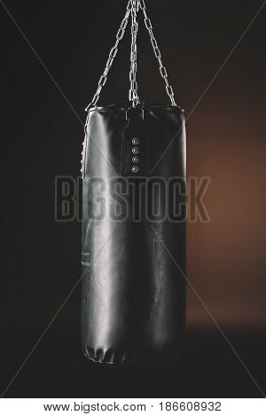 Close-up view of black punching bag hanging in darkness action sport concept