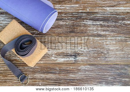Accessories or props for yoga pilates or fitness. Exercise lilac mat two cork blocks and grey strap on wooden background.Copy space.