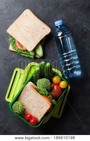 Lunch box with sandwich and vegetables. Top view