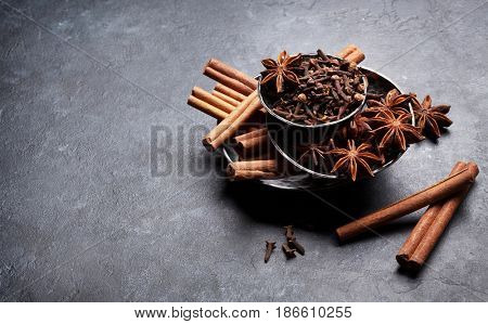Various spices bowls over stone background. Cinnamon, anise, clove. With copy space