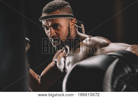 Portrait Of Angry Muay Thai Fighter Training Isolated On Black