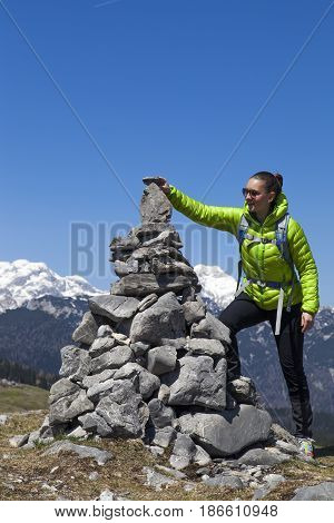 Happy smiling young woman hiker putting stones, small rocks on stone stack in mountain nature landscape in Slovenian Alps, against  bright blue sky. Space for text