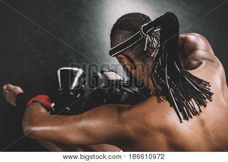 Back View Of Muay Thai Fighter With Mongkhon On Head Sitting On Floor