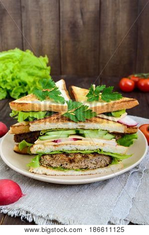Multilayered sandwiches with a juicy cutlet cheese radish cucumber lettuce arugula cutting in half on a plate on a dark wooden background. Vertical view