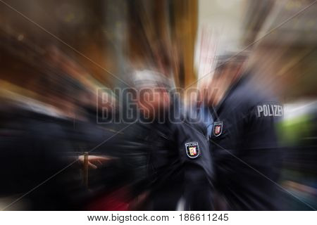 German police officers in action focus on the POLIZEI emblem on the uniform blurred crowd and surrounding background with zoom effect copy space