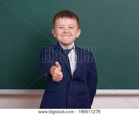 school boy show best gesture, portrait near green blank chalkboard background, dressed in classic black suit, one pupil, education concept