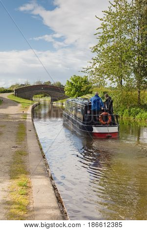 Saint Martins Shropshire UK - May 14 2017: A narrowboat on the Shropshire Union canal in the vicinity of the New Marton upper locks an idyllic vacation and alternative lifestyle on the waterway network