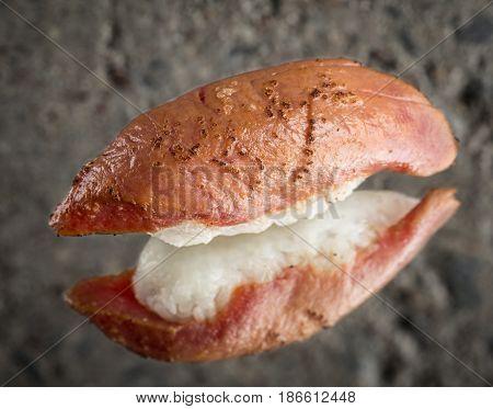Burned nigiri sushi with tuna over concrete background