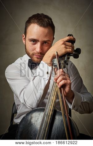 Caucasian handsome male playing on antique black cello