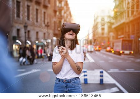 Future is here young woman is amazed and excited by her new present virtual reality glasses she sees images and augmented reality