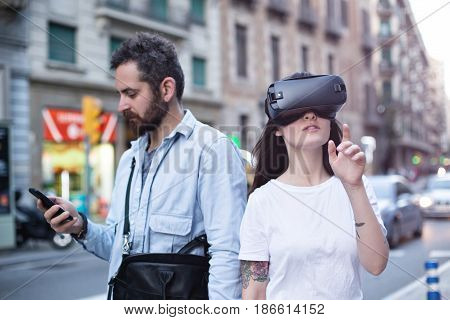 Authentic and trendy couple of millenials use augmented reality technology and VR headset in the busy city street
