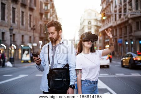 Handsome man and his girlfriend explore future world of immersive technology in the bust street with smartphone and VR googles